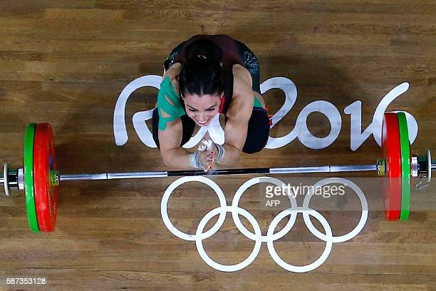 Mexico's Monica Patricia Dominguez Lara reacts while competing in the Women's 58kg weightlifting competition at the Rio 2016 Olympic Games in Rio de...