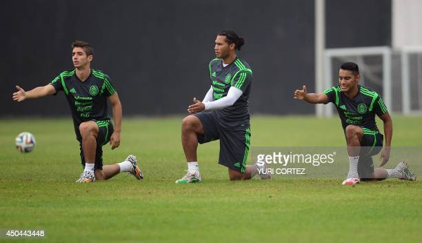Mexico's national football squad midfielders Isaac Brizuela and Jose Juan Vazquez stretch with defender Carlos Salcido during a training session at...