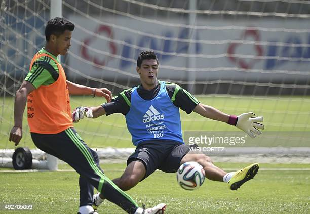 Mexico's national football team forward Raul Jimenez acting as goalkeeper attemps to stop a ball during a training session at the High Performace...