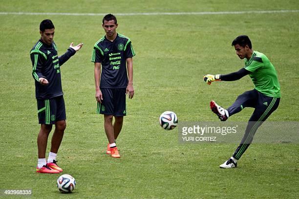 Mexico's national football team goalkeeper Alfredo Talavera kicks a ball in front of teammates Raul Jimenez and Paul Aguilar during a training...