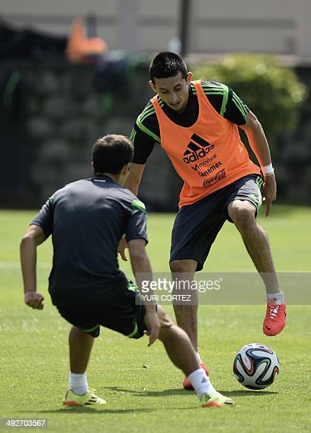 Mexico's national football team Hector Herrera disputes the ball with teammate forward Isaac Brizuela during a training session at the High...