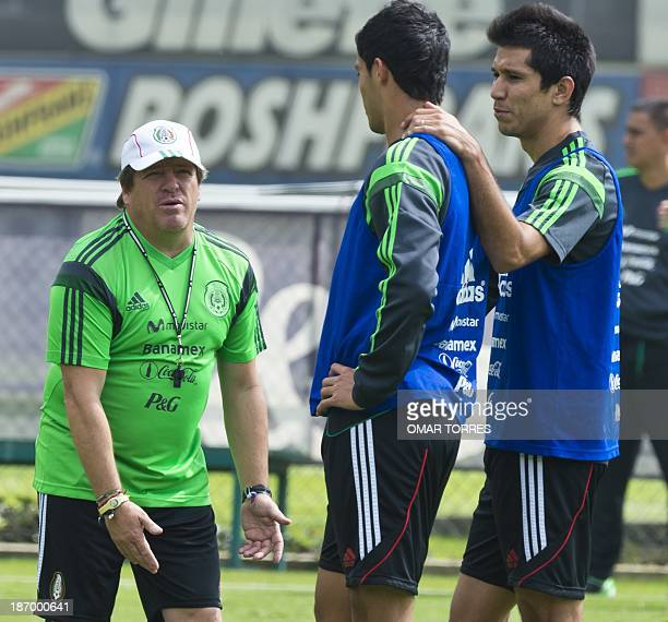 Mexico's National team coach Miguel Herrera gestures in front of Raul Jimenez and Jesus Molina during a training session on November 05 2013 in...