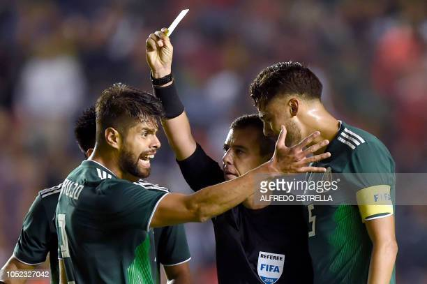 Mexico's Nestor Araujo and Diego Reyes argue with referee Joel Aguilar during the friendly football match between Mexico and Chile at the La...