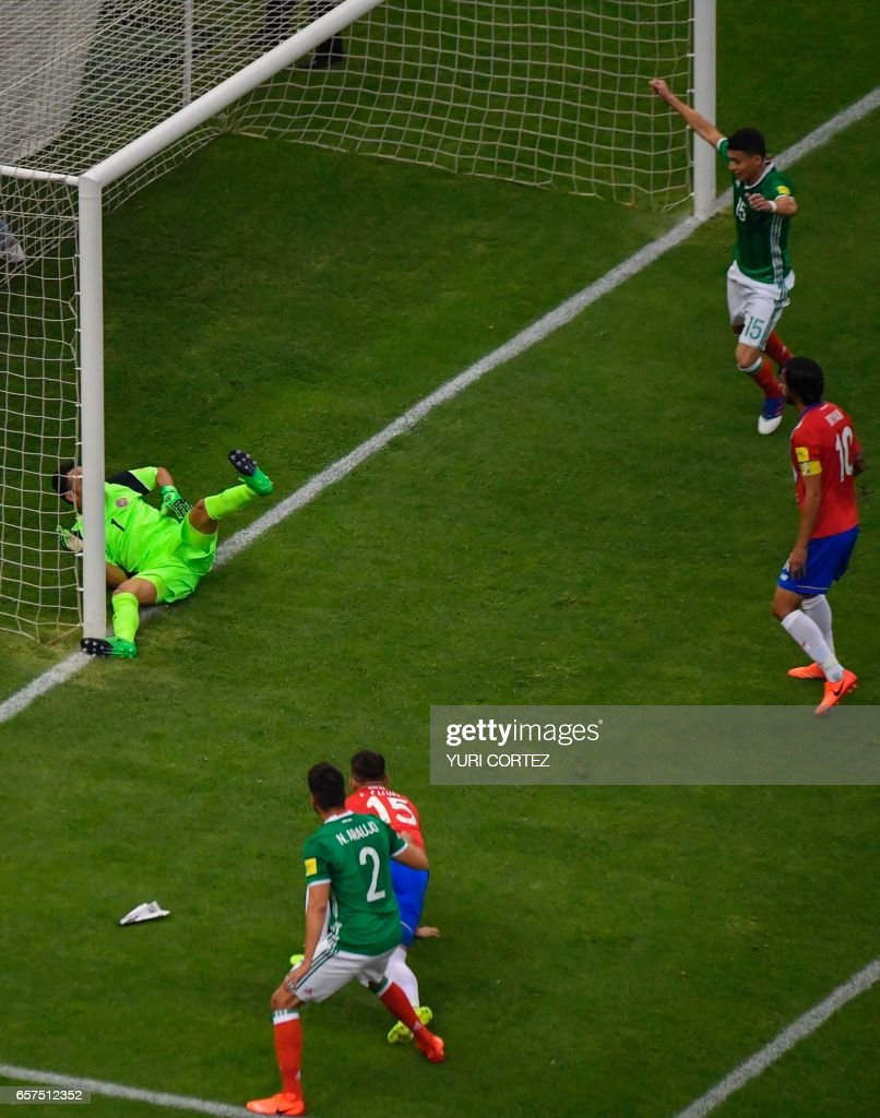 Mexico's Nestor Araujo (bottom) scores against Costa Rica's goalkeeper Keylor Navas during their 2018 FIFA World Cup qualifier football match in Mexico City on March 24, 2017. /