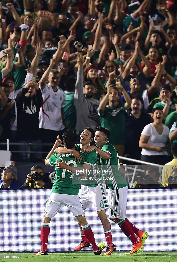 Mexico's Oribe Peralta (L) celebrates with Hirving Lozano and Hector Herrera (R) after scoring the team's second goal against Jamaica during the Copa America Centenario football match in Pasadena, California, United States, on June 9, 2016. / AFP / Frederic J. Brown