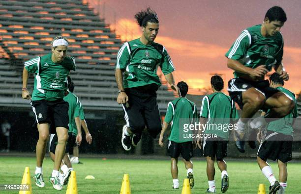 Mexico's players Adolfo Bautista Rafael Marquez and Francisco Rodriguez jump during a Copa America training session in Puerto La Cruz Venezuela on...