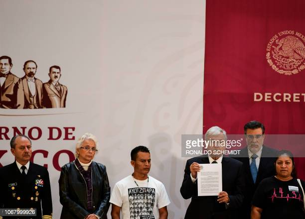 Mexico's President Andres Manuel Lopez Obrador shows the signed decree to investigate the case of 43 missing students during a ceremony with...