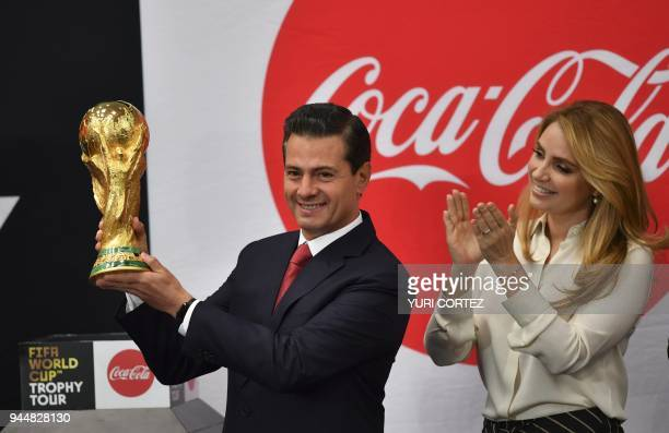 Mexico's President Enrique Pena Nieto accompanied by his wife Angelica Rivera holds the FIFA World Cup trophy while it is displayed at the...