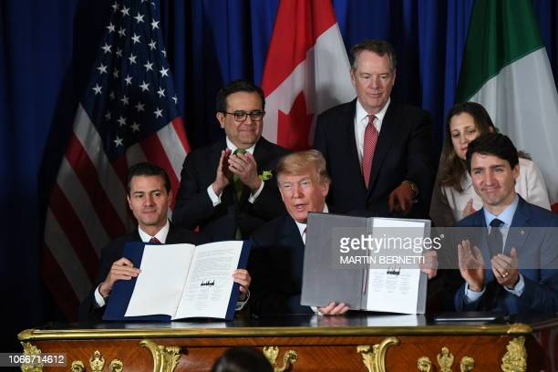 TOPSHOT Mexico's President Enrique Pena Nieto US President Donald Trump and Canadian Prime Minister Justin Trudeau are pictured after signing a new...