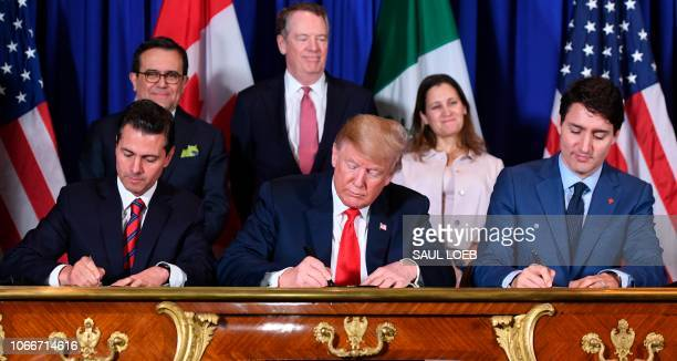 TOPSHOT Mexico's President Enrique Pena Nieto US President Donald Trump and Canadian Prime Minister Justin Trudeau sign a new free trade agreement in...