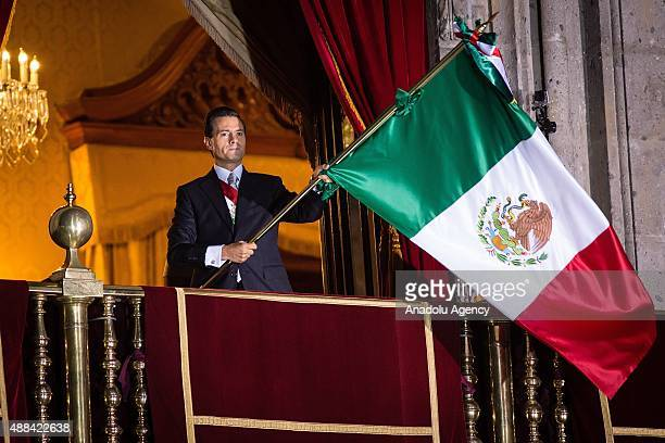 Mexico's President Enrique Pen–a Nieto waves a Mexican flag after giving the traditional 'El Grito' during the anniversary of the 'Grito de Dolores'...