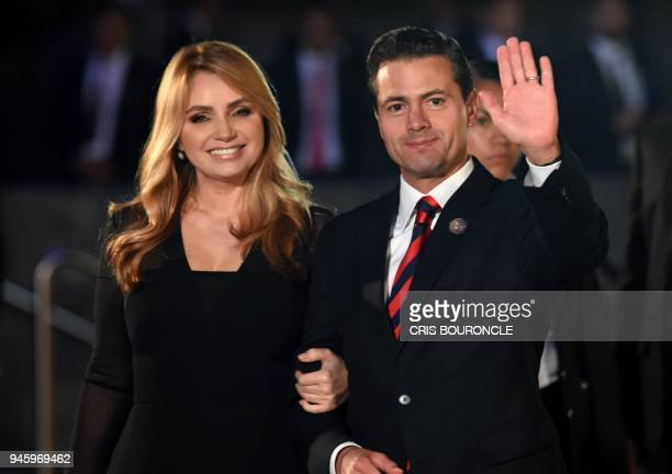 Mexico's President Enrique Pena Nieto waves next to his wife Angelica Rivera upon arrival at the National Theatre in Lima to attend the Eighth Summit...