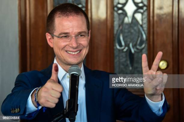 Mexico's presidential candidate Ricardo Anaya for the 'Mexico al Frente' coalition party shows his inked finger and flashes the victory sign after...