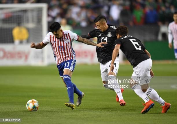 Mexico's Roberto Alvarado and Jonathan Dos Santos pressure Paraguay's Hernan Perez during the international friendly match between Mexico and...