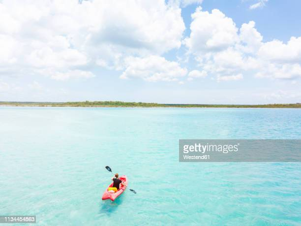 mexiko, yucatan, quintana roo, bacalar, woman in kayak on the sea in turquoise water, drone image - kayaking stock pictures, royalty-free photos & images