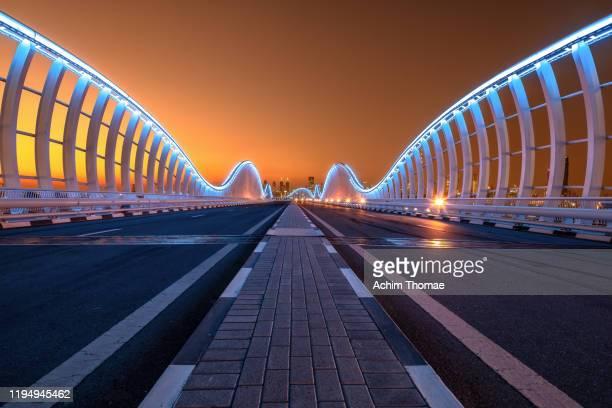 meydan bridge; dubai, united arab emirates - dubai stock pictures, royalty-free photos & images