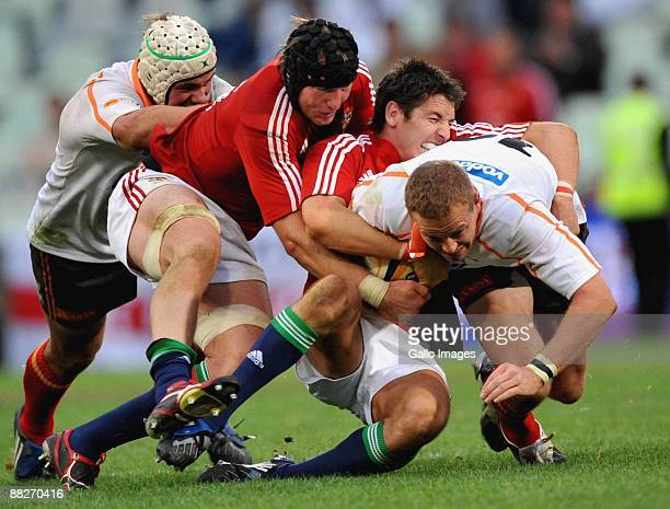 Meyer Bosman of the Cheetahs is stopped by Stephen Ferris and James Hook of the British & Irish Lions during the British and Irish Lions Tour match...