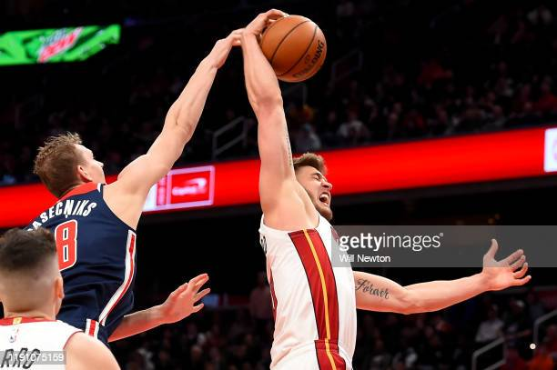 Meyers Leonard of the Miami Heat rebounds in front of Anzejs Pasecniks of the Washington Wizards during the second half at Capital One Arena on...