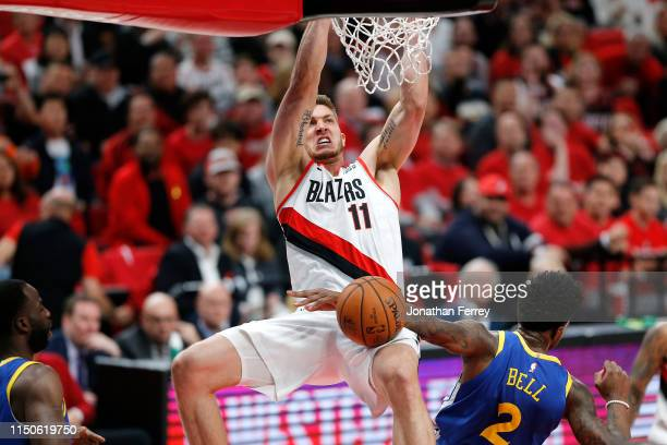 Meyers Leonard of the Portland Trail Blazers dunks the ball against Jordan Bell of the Golden State Warriors during the first half in game four of...