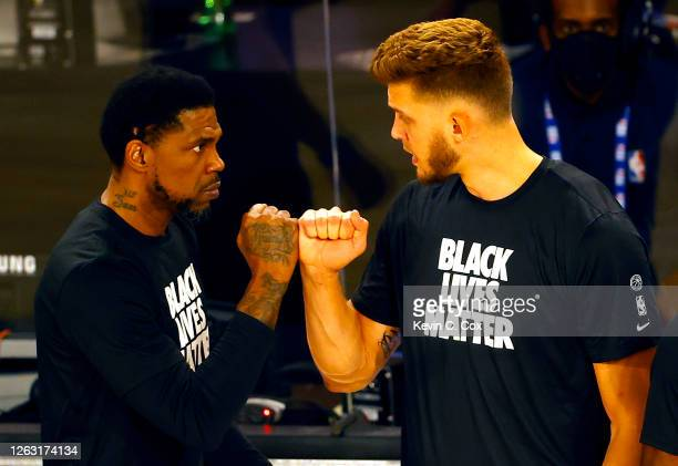 Meyers Leonard right and Udonis Haslem of the Miami Heat bump fists after Leonard stood during the National Anthem before the start of a game against...