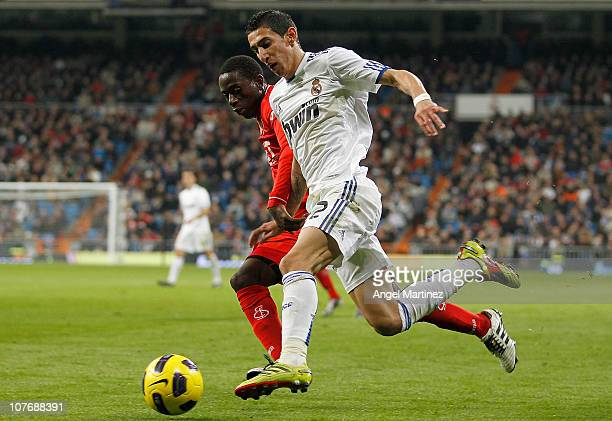 Mezut Ozil of Real Madrid duels for the ball with Mauhamadou Dabo of Sevilla during the La Liga match between Real Madrid and Sevilla at Estadio...