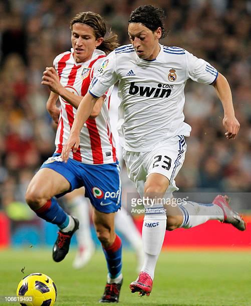 Mezut Ozil of Real Madrid is chased by Filipe Luis Kasmirski of Atletico Madrid during the La Liga match between Real Madrid and Atletico Madrid at...