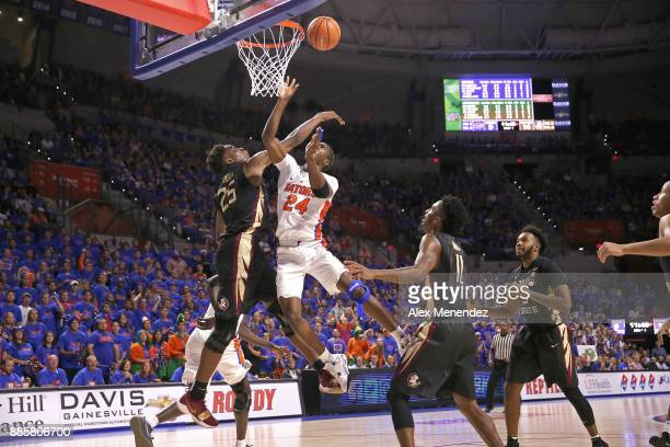 Mfiondu Kabengele of the Florida State Seminoles blocks a shot against Deaundrae Ballard of the Florida Gators during a NCAA basketball game at the...