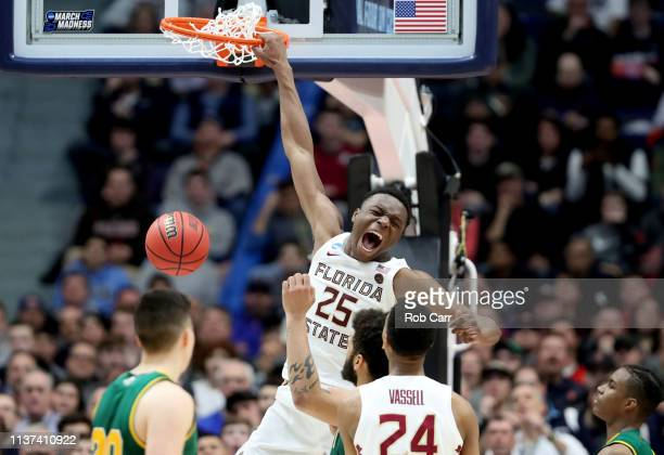 Mfiondu Kabengele of the Florida State Seminoles celebrates after he dunks the ball against the Vermont Catamounts during their first round game of...