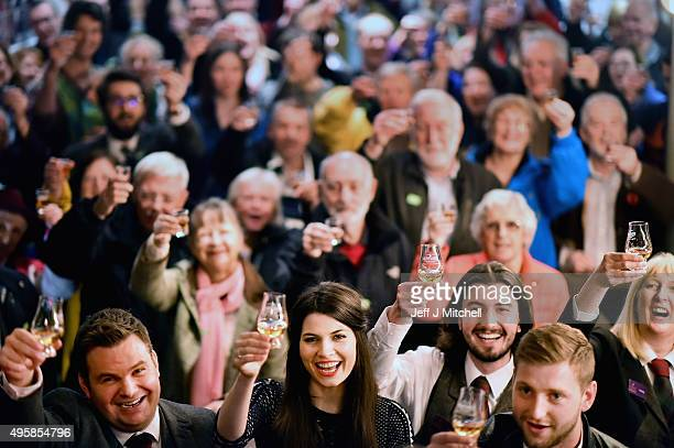 Mhairi Fergusson joins members of the public as they hold up whisky glasses at Glenturret Distillery in an attempt to set a record for the most...
