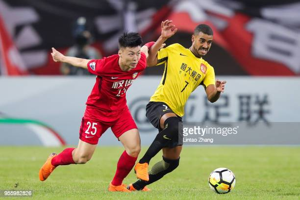 Mi Haolun of Tianjin Quanjian competes the ball with Alan of Guangzhou Evergrande during the AFC Champions League Round of 16 first leg match between...
