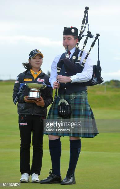 Mi Hyang Lee of Korea winner of the Aberdeen Asset Management Ladies Scottish Open poses for a photograph with a bag piper on the 18th green after...