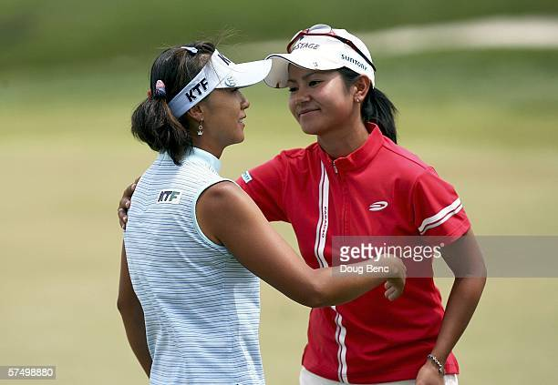 Mi Hyun Kim of South Korea is congratulated by Ai Miyazato of Japan on the 18th green after her victory on the final day of the Ginn Clubs Resorts...