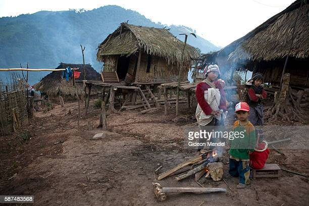 Mi teu and Miti warm themselves around a fire at dawn in the Ban Nam Lai Akha village at dawn The Akha are a hill tribe of subsistence farmers known...