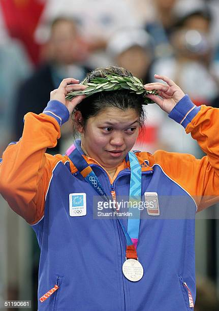 Mia Audina of the Netherlands adjusts her olive leaf wreath after receiving the silver medal for the women's singles badminton event on August 19...