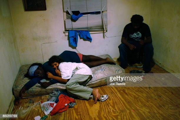 Mia Dennis, Annie Thomas and Brandon Brown sit in the former bedroom of Mia in the foreclosed home that they reoccupied with their family after...