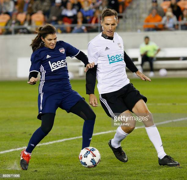 Mia Hamm attempts to hold off Steve Nash as she brings the ball up the field during the Kick In For Houston Charity Soccer Match at BBVA Compass...