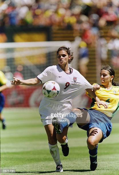 Mia Hamm of Team USA gets contact from Juliana of Team Brazil as they jockey for the ball during the Women's World Cup game at Stanford Stadium on...