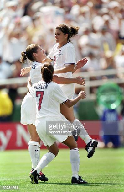 Mia Hamm of Team USA is embraced by teammates Shannon MacMillan and Sara Whalen after making her penalty kick against Team China in the Final match...