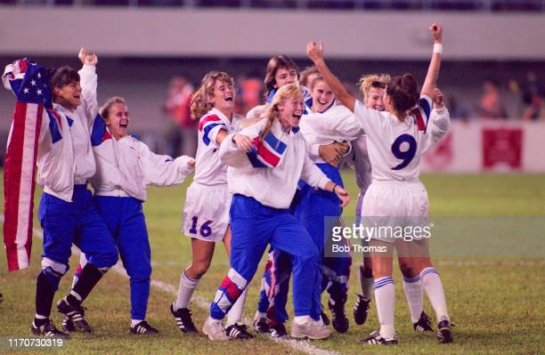 Mia Hamm raises her arms in the air as her team mates rush forward to celebrate after the United States beat Norway 2-1 in the final of the 1991 FIFA...