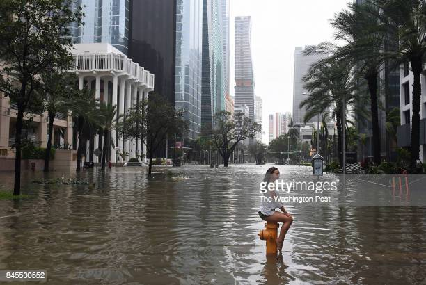 Mia Herman has an acquitance take a photo of her sitting on a fire hydrant on a flooded street as Hurricane Irma hits the area on Sunday September 10...