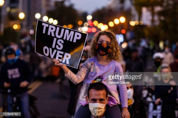 """Mia holds a sign reading """"Trump Is Over"""" as she sits on the shoulders of her father, Todd, during a demonstration at the Black Lives Matter Plaza in..."""
