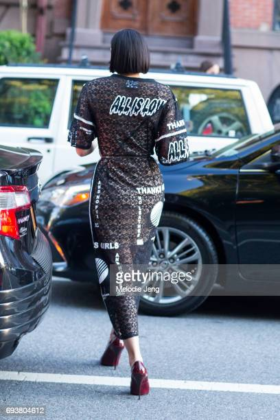 Mia Moretti wears a Spring/Summer 2017 Cotton lace midi Stella McCartney Camellia black dress with All is Love and Thanks Girls text outside the...