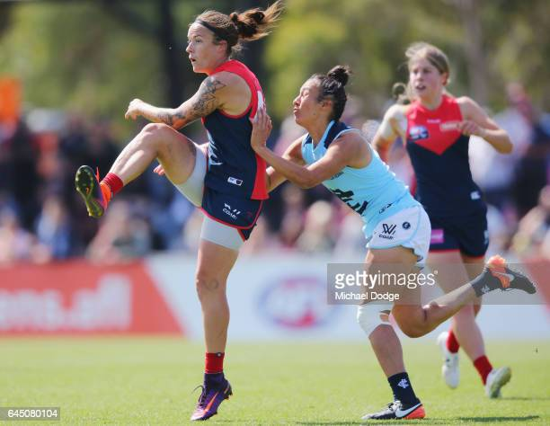Mia RaeClifford of the Demons kicks the ball away from Darcy Vescio of the Blues during the round four Women's AFL match between the Melbourne Demons...