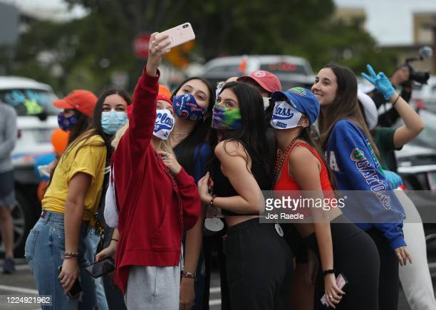 Mia Sanford graduating from Dr Michael M Krop Senior High School takes a selfie picture with friends before participating in a parade of vehicles...