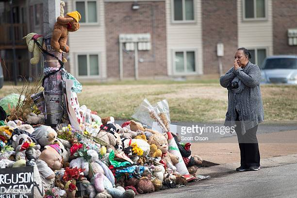 Mia Swisher says a prayer during a visit to a memorial to Michael Brown outside the Canfield Green apartments where he was shot and killed by a...