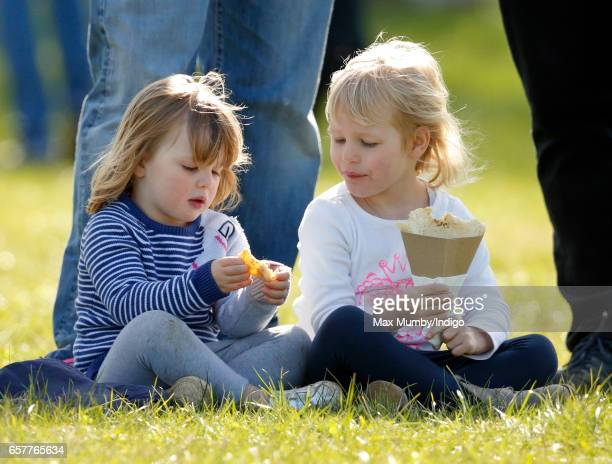 Mia Tindall and cousin Isla Phillips eat crepes as they attend the Gatcombe Horse Trials at Gatcombe Park on March 25, 2017 in Stroud, England.