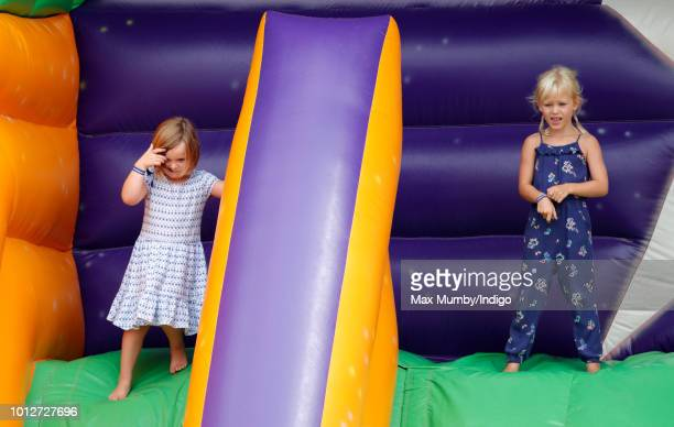 Mia Tindall and cousin Isla Phillips play on an inflatable bouncy slide as they attend day 1 of The Festival of British Eventing at Gatcombe Park on...