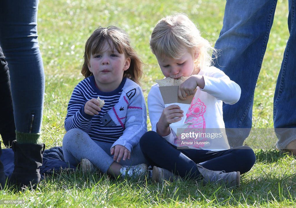 Mia Tindall (L) enjoys a snack with her cousin Isla Phillips during the Gatcombe Horse Trials at Gatcombe Park on March 25, 2017 in Stroud, England.