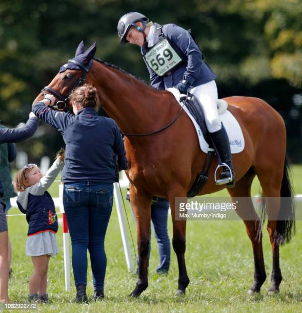 Mia Tindall feeds grass to her mother Zara Tindall's horse 'High Kingdom' after she competed in the dressage phase of the Whatley Manor Horse Trials...