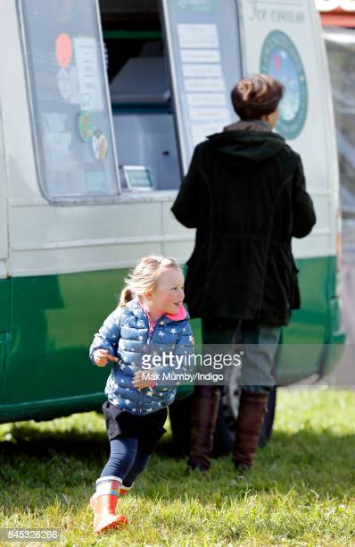 Mia Tindall runs around whilst her grandmother Princess Anne Princess Royal talks with an ice cream vendor as they attend the Whatley Manor Horse...